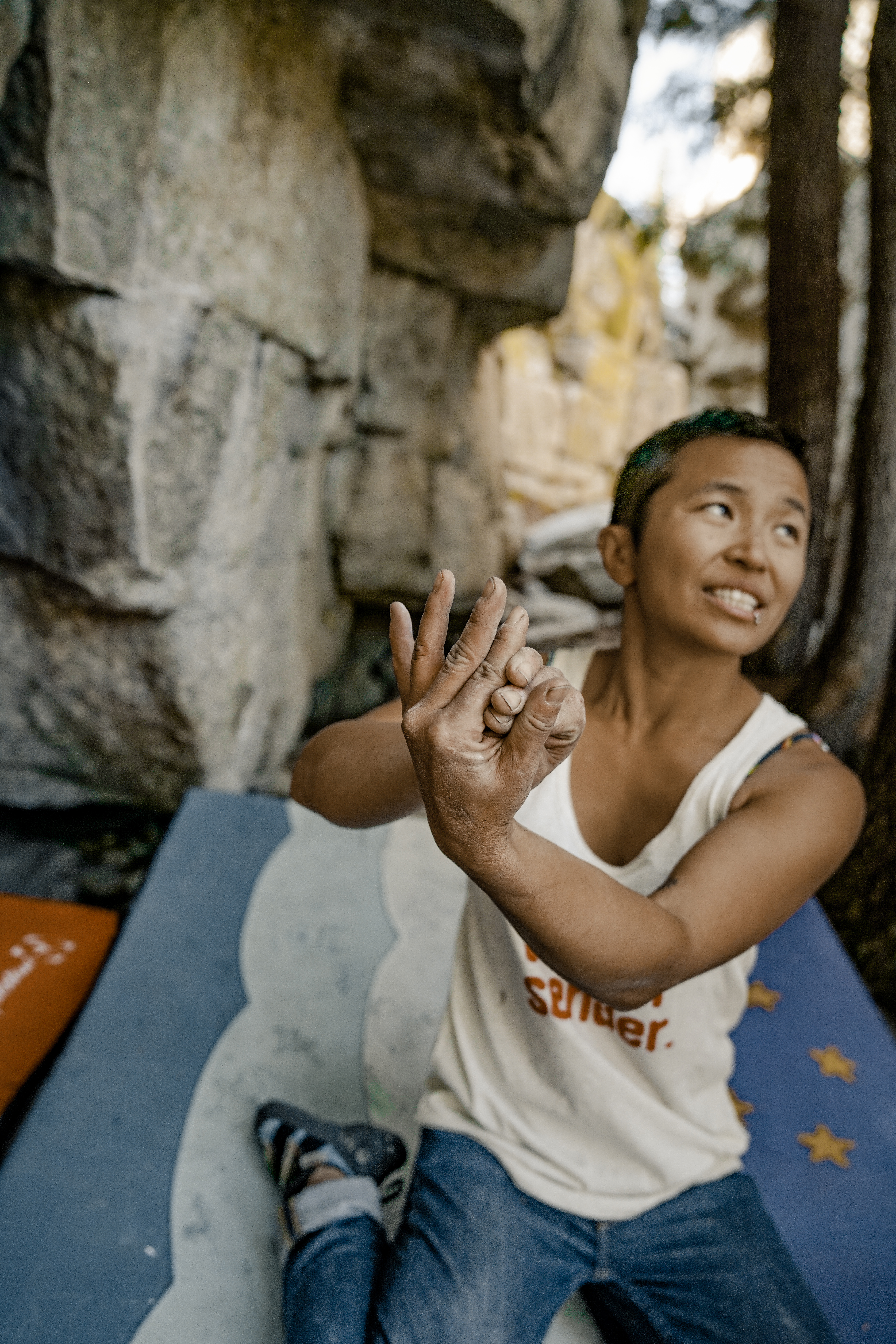 Narinda kneels on a crashpad beneath a granite boulder, using her hands to demonstrate wedging fingers into a crack.