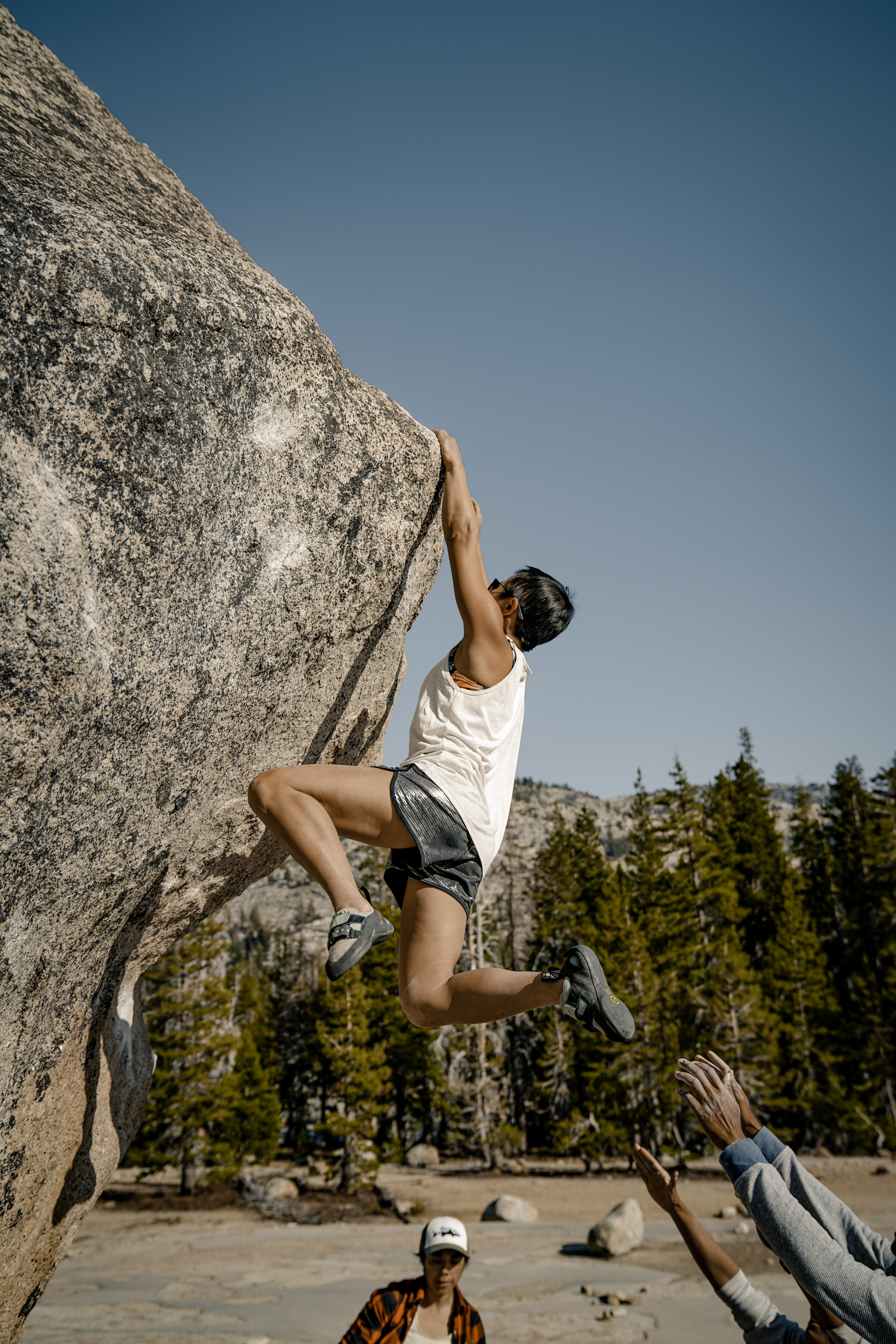 Narinda in a tank top and shiny shorts, feet swinging away from the overhanging granite boulder as she clings to the rock above.