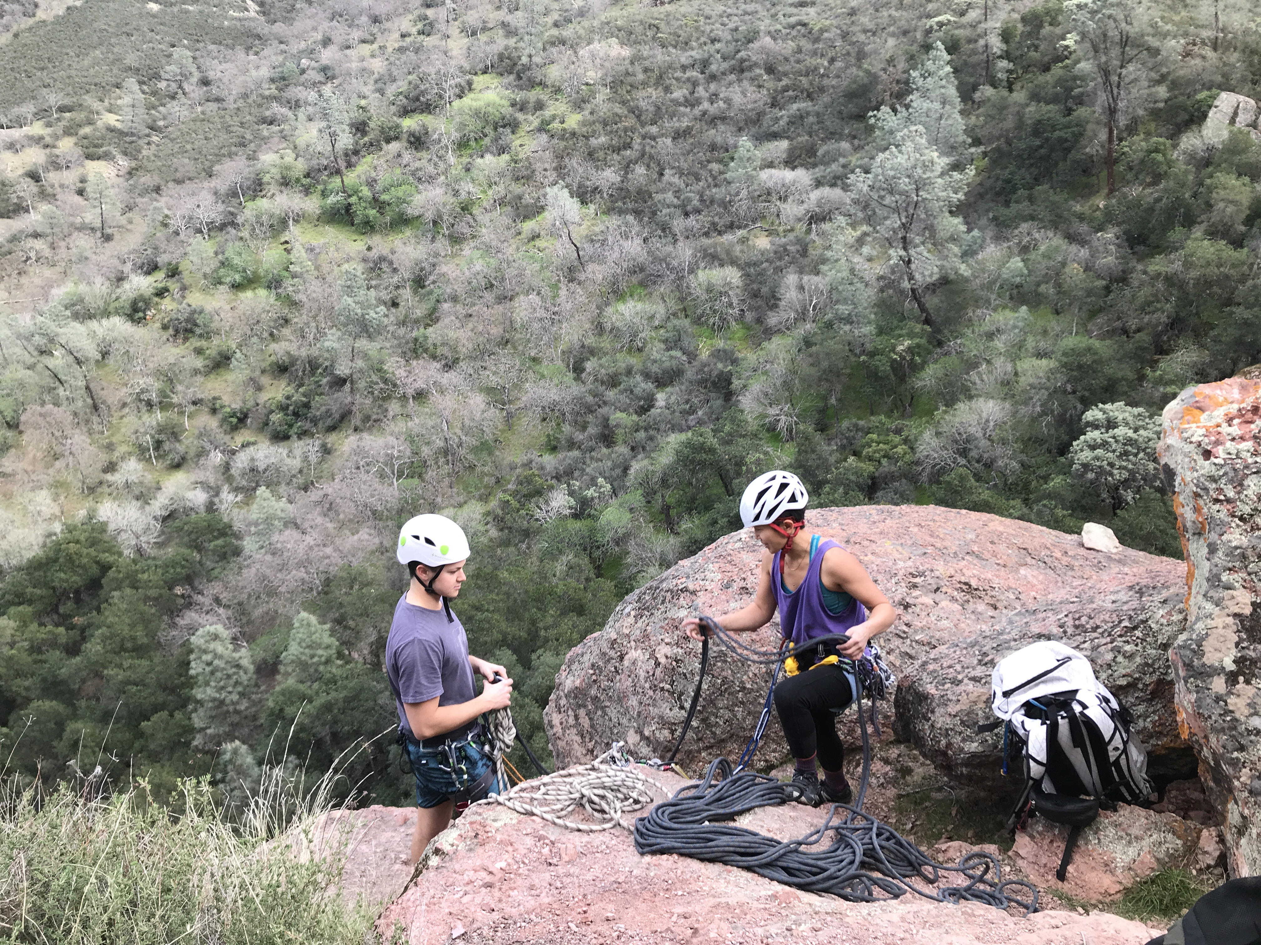 Narinda teaching a student to build a top-rope anchor above a rock climb.